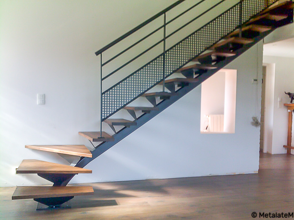 Escalier tournant bas à limon central avec marches en bois.