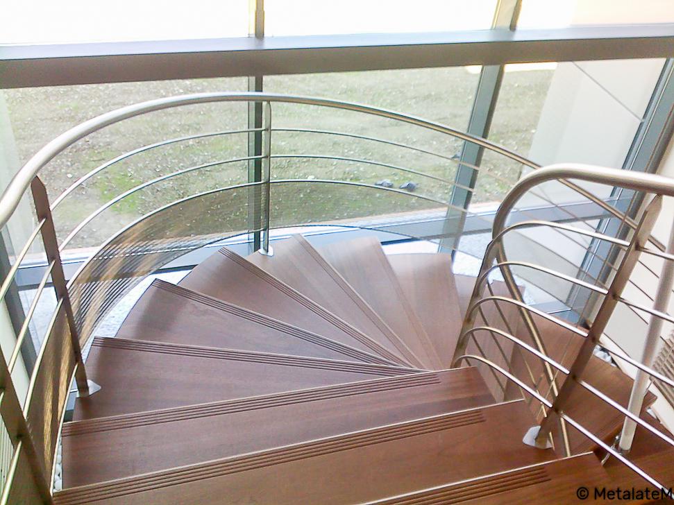 Escalier sur plusieurs niveaux avec rampe continue inox et marches en bois.