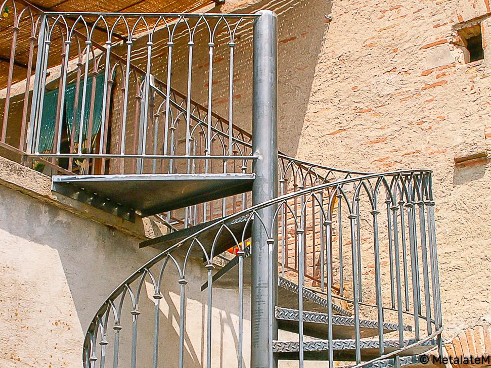 Escalier hélicoîdal d'extérieur en métal et rampe en fer forgé.
