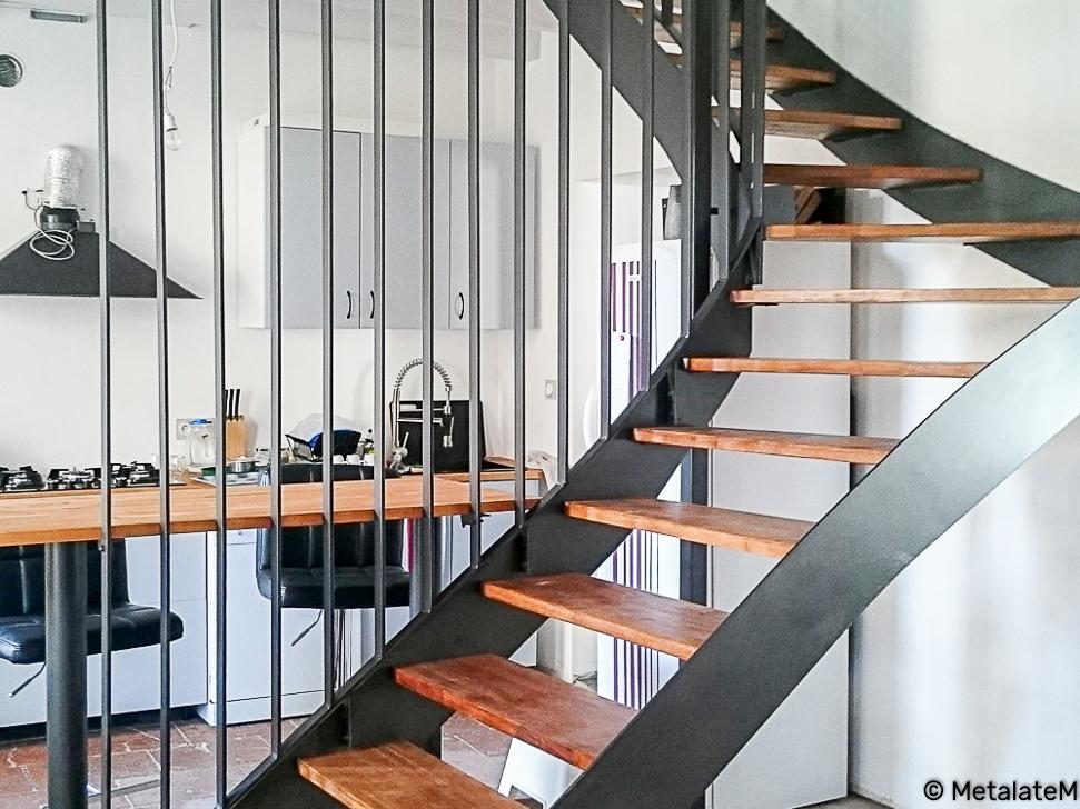 Escalier design en métal à quart tournant. Deux limons à la Française et un garde corps toute hauteur.
