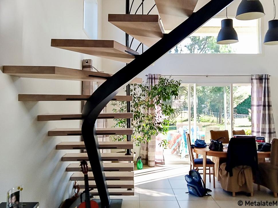Escalier quart tournant à limon central caissonné et marches en bois.