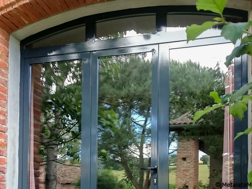 Porte d'entrée vitrée avec une imposte arrondie.